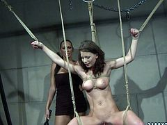 Submissive brunette amateur gets suspended in the air with her slender body fully tied with a thick rope before a kinky domina slaps her body with a batt in BDSM-styled sex video by 21 Sextury.