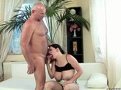 Immense brunette amateur BBW goes down on her knees to suck slim cock of a horny grandpa before he clings to her big round tits to oral caress it with pleasure.