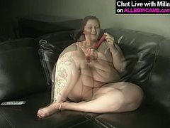Dirty BBW whore with fat ass and bigguns is sitting naked on a leather couch in front of the camera. She stuffs her cunt with smooth sex toy pleasing her pussy with dildo.