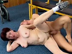 This lustful granny gives a blowjob to much younger dude in the gym. Later on she lies down on the floor and gets her old pussy fucked hard.
