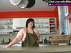 Horny mom with big boobs and fat ass leans over the kitchen counter while fondling her pussy with fingers. Kinky solo masturbation video is presented to you by All BBW Cams.