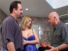 Kitty Johnson is wearing seductive blue lacy corset and thongs. She flashes her boobs in front of three horny men in the bathroom. Then Kitty kneels down gives stout blowjob to one of the guys.