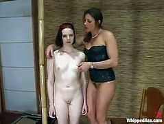 Cute redhead girl Claire Adams is having fun with horny dominatrix Kym Wilde. Kim rubs Claire's tits and pussy and then slaps her nice ass as hard as she can.