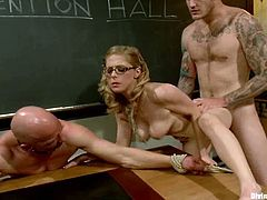 Chad Rock and Christian Wilde are playing BDSM games with some slutty pigtailed blonde. The hussy and the tattooed guy tie the bald nerd up and humiliate him in many ways.