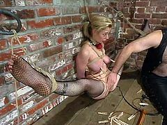 Girl in fishnet stockings loves, when her master spanks her ass, having her tied up and suspended. Then he plays with her muff, attaching some twitches on her twat lips.