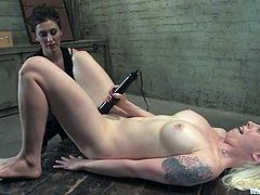 Lorelei Lee spreads her legs wide apart and allows some brunette to attach wires to her body and slam her shaved pussy with a dildo.
