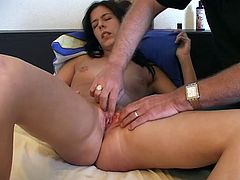 Salacious brunette Joel is lying on a bed with her legs moved wide apart and allows some dude to oil her snatch and rub it with his fingers.