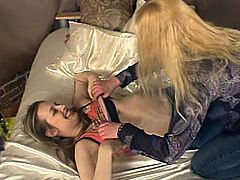 Two kinky blonde chicks are having lesbian fun indoors. They make out and fondle each other awkwardly and then use a dildo to satisfy each other.