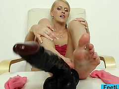 Incredible hot blondie sits down takes off her socks to oil her sexy feet and sole. After that, she strokes a dildo with her foot