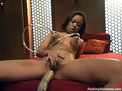 Slutty Asian girl Annie Cruz is playing with a fucking machine in a bedroom. She gets her boobs pumped and then gets her snatch smashed by the device.