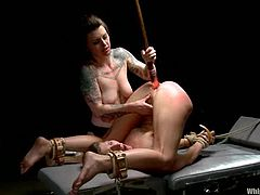 Chained girl gets punished by her mistress. She gets whipped and fingered. Later on she gets her pussy toyed with a strap-on and ass with massive dildo.