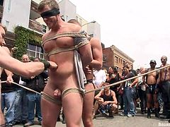 He's a very pretty boy and luckily, the guys have blindfolded him, so he won't see that crowd, that's staring at him. The sexy gay is completely naked and tied with rope, as his friends give the crowd an interesting show, using his hot body.