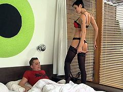 Horny MILF in red lingerie and stockings gives a blowjob to younger guy. After that she gets fucked in a sideways position.