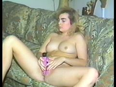 A kinky long-haired blonde is having fun in the living room. She pleases herself with fingering and then smashes her coochie with a dildo.