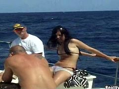 Lustful brunette babe gives a blowjob on a yacht deck. Later on she gets fingered and then fucked in her shaved pussy.