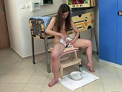Slim and pretty brown-haired girl strips her clothes off. She sits down on a chair and shaves her bushy pussy.