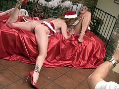 Sexy Silvia Saint and Tara White in Xmas hats kiss lying on a sofa. Then they start to lick boobs and finger pussies.
