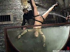 Sexy bitch Nicolette gets shackled by a mistress in a basement. Then she gets her cunt toyed and takes a swim in a glass box filled with water.