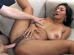 Stunning brunette MILF with big boobs gets her pussy licked. Then she lies down on a sofa and gets fucked by big cocked guy.