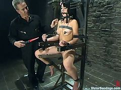 Sexy woman Riley Mason is bound with cuffs and chains, and tied to a chair. Her master takes multiple hoses and sprays her with freezing cold water. She is shivering and make up is running down her face.