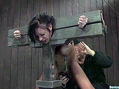 Brunette girl gets restrained with the stocks. The guy also fixes claws to her tits. Then he toys her pussy with a vibrator from behind.