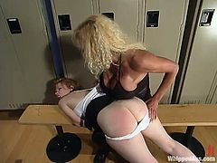 Locker room was spotted as a place for some lesbian BDSM. Girls are done with the gym and this milf is going to trap one and fuck her with a strapon!