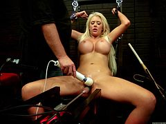 Sexy blonde Courtney Taylor gets tied up by some guy indoors. The dude strokes Courtney's big fake tits and then stuffs the babe's pussy with a dildo.