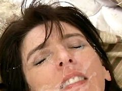 A lewd dark-haired milf is playing dirty games with two guys in the bedroom. She sucks and rides their wangs and then gets her holes pounded at the same time and gets her face covered with cum.