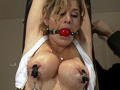 Stunning blonde girl gets gagged and tied up in the gym. She gets her wet pussy fucked by the fucking machine and also a guy fixes clothespins to her body.