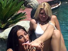 Tiffany Taylor and Staci Thorn have a rest in backyard. They take sunbathes and read some book. After some time they take bikinis off and lick each others toes.