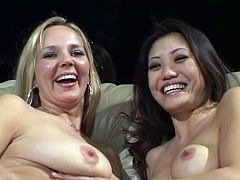 White and Asian pose for the camera showing their tits. Then they lie down on a sofa and spread legs. After that they start to toy their wet pussies with big dildos.
