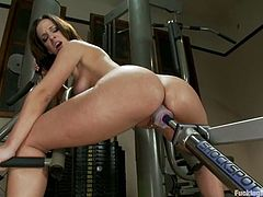 Amazingly hot brunette babe lies on a training device in a gym. She spreads her legs and gets her wet vagina stuffed with the fucking machine.