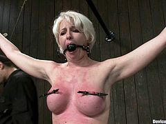This busty and sexy blond babe Devon Taylor gets suspended up high. Then her master ties her tits up and twitches them, getting her body turn red from pain!