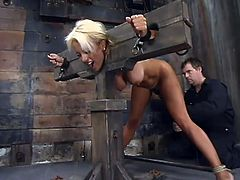 Naughty blonde chick in the stocks gets toyed from behind. Later on she also gets tied up with straps and tortured with claws fixed to her nipples.
