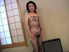 This mature Asian woman is wearing a fishnet bodystocking with an opening to her hairy crotch. A guy is pleasuring her by toying her old cunt with a vibrator.