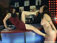Sexy Alsana gets undressed and then spanked on a bar counter. After that she also gets her wet pussy drilled with a strap-on by Selina.