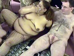 Curly slut with big saggy tits, fat belly folds and cellulite ass is wearing fishnet stockings. Nikki is taking part in kinky FFM threesome porn scene. So watch her sucking hard dick while getting pleased by another woman.