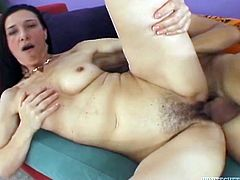 Kinky brunette MILF sucks big cock standing on her knees and plays with her pussy. After that she lies down on a bed and gets fucked in her bushy pussy.