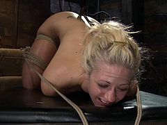 She doesn't look charming anymore, when she gets bondaged and hooked on her ass! Pain makes her do some weird sounds.