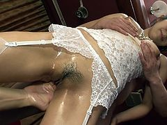 Tempting Japanese dark haired mommy in white lacy lingerie keeps moaning with pleasure while two mean guys finger bang her sweaty hairy snatch in turn.
