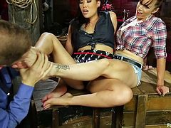 Wolf is worshiping London and Bella's toes by running his tongue all over them. They enjoy the foot licking and decide to reward him by giving him a nice feetjob. They pull his cock out and pleasure him with their feet while they finger each other.