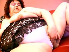 Brunette BBW lifts the dress up and fondles her pussy. After that she also licks a dildo to make it wet and toys herself lying on a sofa.