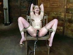 Sexy blonde girl sits on a chair being gagged and tied up. The master fingers Ela's ass and toys the pussy with a fucking machine.