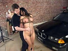 Tied up Asian girl lies on a BMW hood and gets her hairy pussy clothespinned. After that this girl gets whipped and watered with powerful jet of water.