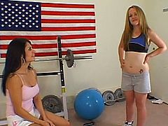 A cute blonde and her fabulous brunette GF are having fun in a gym. The lesbians caress each other and then use dildos to fuck each other's shaved pussies.