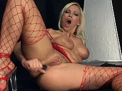 Gorgeous blonde Nicki Hunter takes her miniskirt and top off and demonstrates her big fake tits. Then she pleases herself with fingering and pounds her brown cave with a dildo.