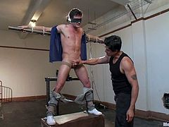 Have a look at this gay bondage scene where this guy is tied up and has a gag-ball places in his mouth before this other due toys around with him.