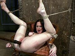 Horny brunette girl lies on a chair being hog tied. The master whips her feet and ass. After that he also fingers and toys her pussy in a rough manner.