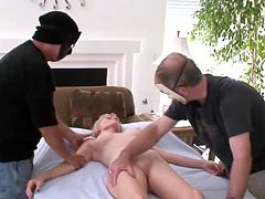 Salacious mature blonde is having fun with two masked men in MMF scene. She sucks and rubs their pricks devotedly and then gets her shaved pussy drilled in missionary position.
