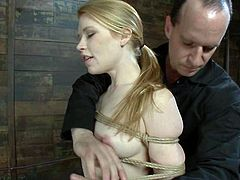 Cute blonde bitch Madison Young allows some guy to tie her up and suspend her in a basement. The man attaches plummets to Madison's nice tits and enjoys the way she moans with pain.